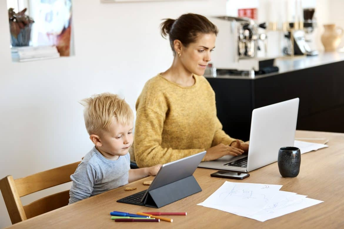 Mother and son using technologies at table