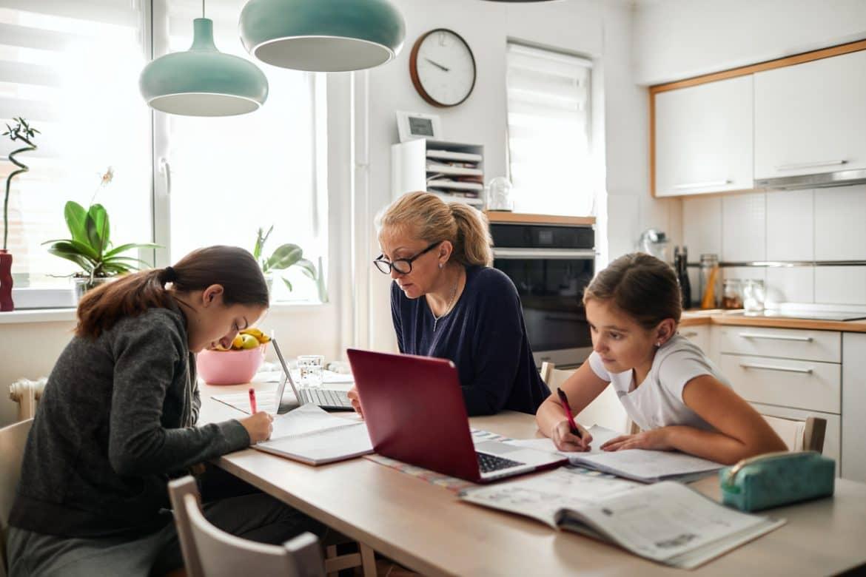Homeschooling – Mother Helping To Her Daughters To Finish School Homework During Coronavirus Quarantine