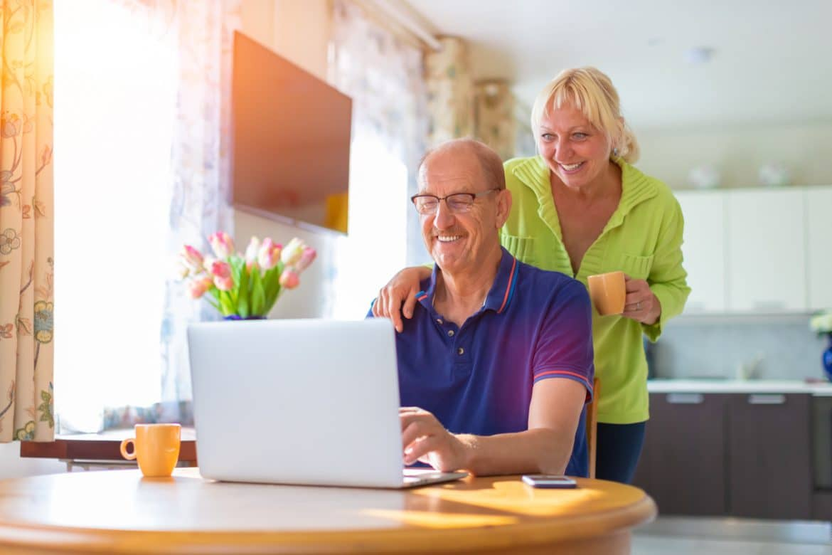 Senior couple looking at the lap top screen smiling and drinking coffee – elderly people video calling or talking by web camera – working at home, freelancing and having hobbies together concept